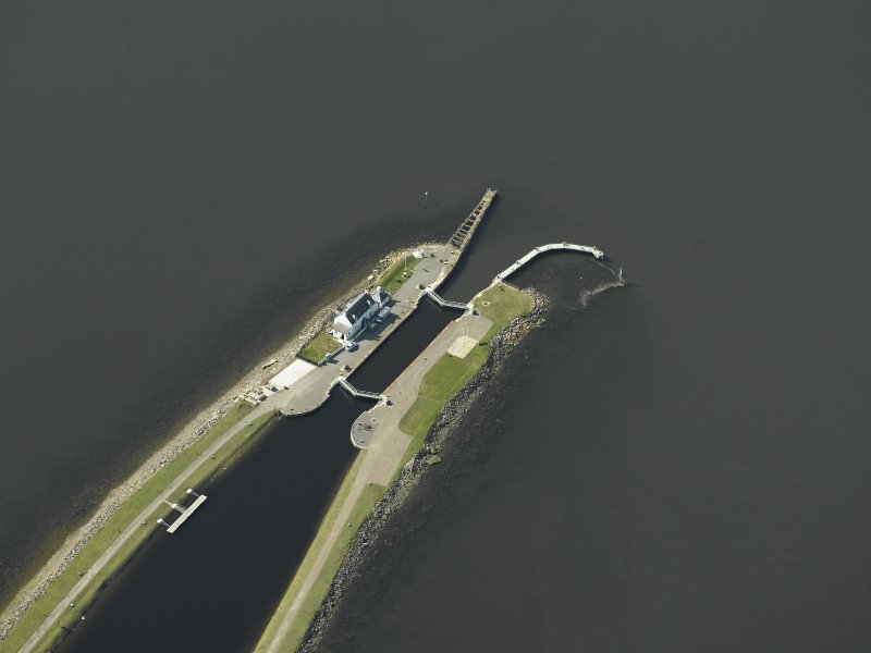 Oblique aerial view centred on the lock, house, piers and beacons, taken from the ENE.