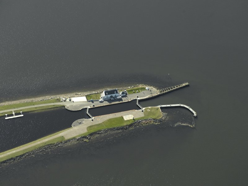 Oblique aerial view centred on the lock, house, piers and beacons, taken from the NNE.
