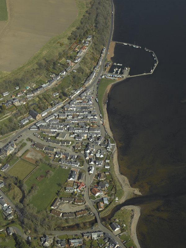 Oblique aerial view of the village centred on the church, harbour, road bridge and hotel, taken from the SW.
