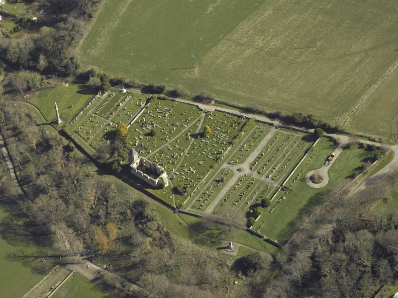 Oblique aerial view centred on the chapel, burial-ground and monument, taken from the NW.