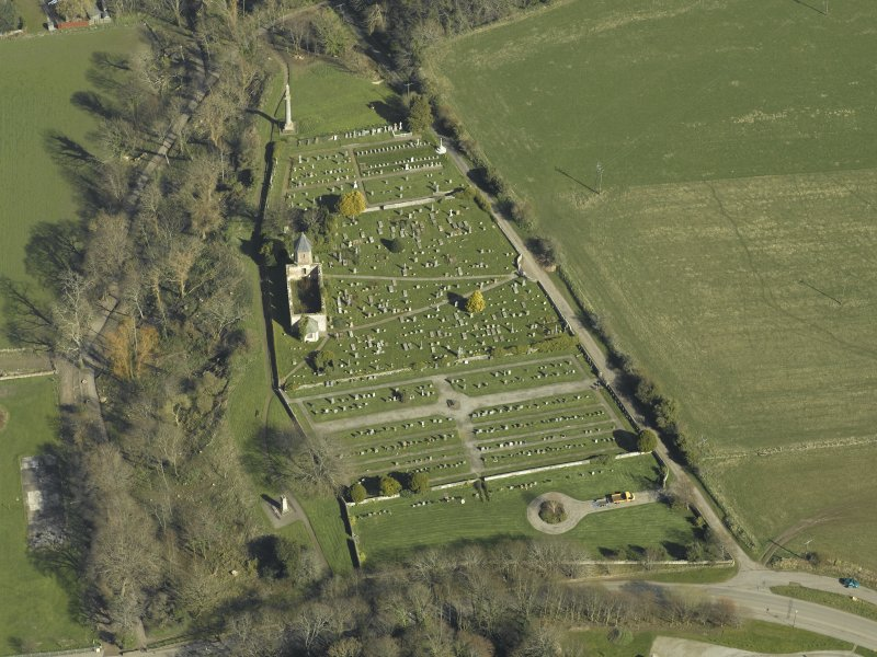 Oblique aerial view centred on the chapel, burial-ground and monument, taken from the WSW.