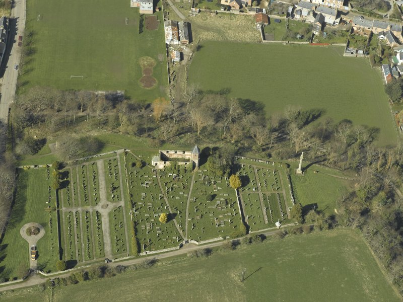 Oblique aerial view centred on the chapel, burial-ground and monument, taken from the SE.