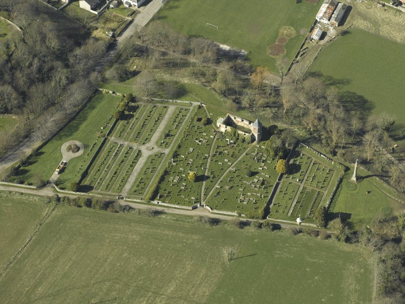 Oblique aerial view centred on the chapel, burial-ground and monument, taken from the ESE.