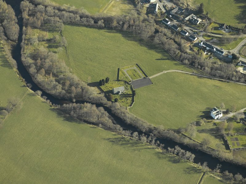 Oblique aerial view centred on the church, burial-ground and manse, taken from the SW.