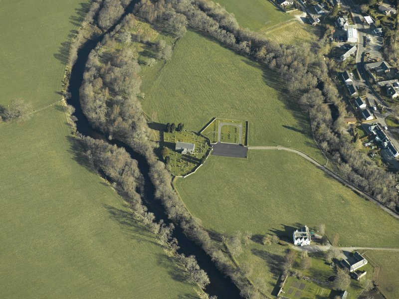 Oblique aerial view centred on the church, burial-ground, stables, farmsteading and manse, taken from the S.