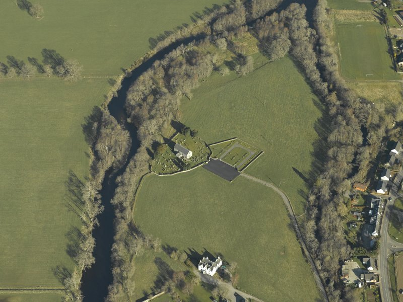 Oblique aerial view centred on the church, burial-ground and manse, taken from the SE.