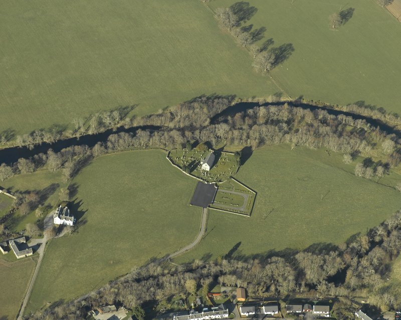 Oblique aerial view centred on the church, burial-ground, stables, farmsteading and manse, taken from the ENE.
