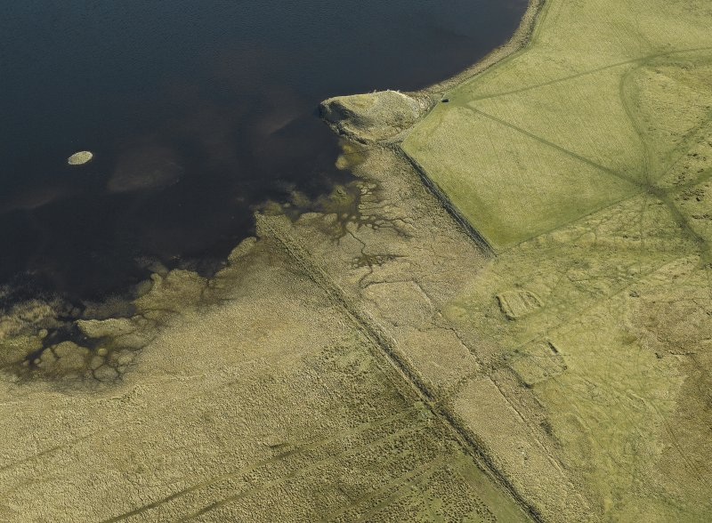General oblique aerial view centred on the remains of the earthwork, bank and the possible island dwelling with the remains of the crannog adjacent and the remains of the buildings and enclosures in the foreground, taken from the WSW.