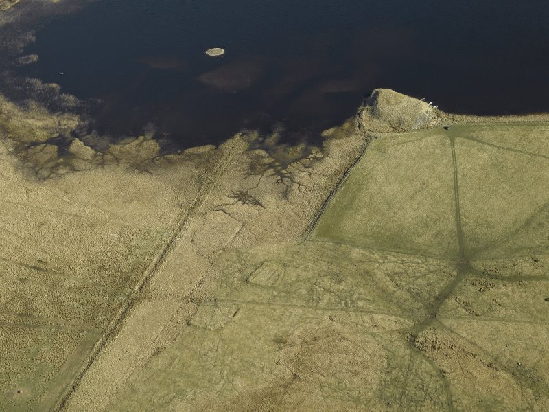 General oblique aerial view centred on the remains of the earthwork, bank and the possible island dwelling with the remains of the crannog adjacent and the remains of the buildings and enclosures in the foreground, taken from the SW.