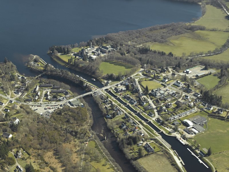 General oblique aerial view of the village centred on the road bridges, swing bridge, locks, abbey and schools, taken from the NW.