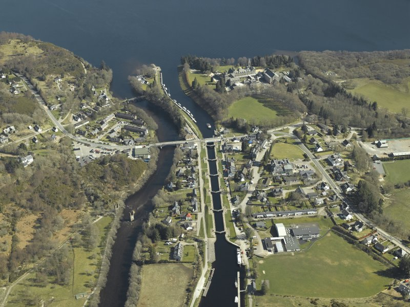 General oblique aerial view of the village centred on the road bridges, swing bridge, locks, abbey and schools, taken from the W.