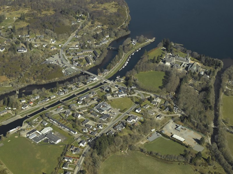 General oblique aerial view of the village centred on the road bridges, swing bridge, locks, abbey and schools, taken from the SW.