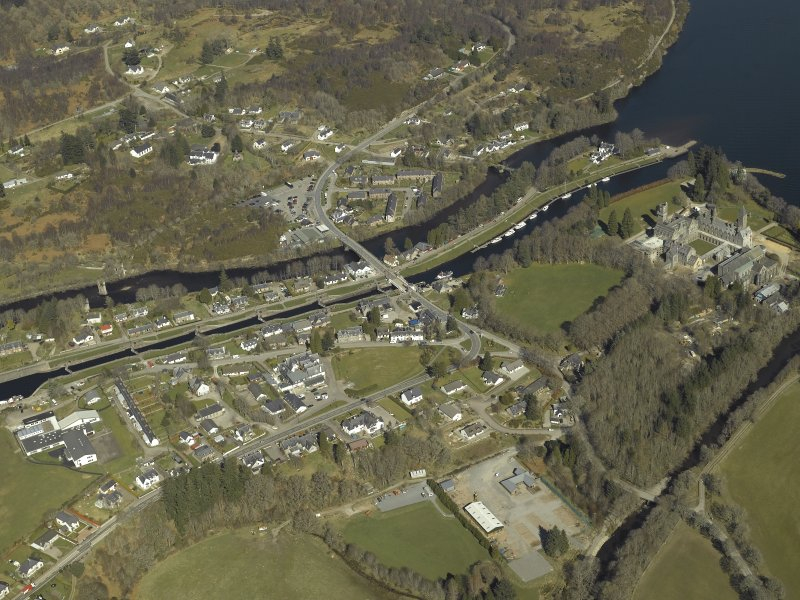 General oblique aerial view of the village centred on the road bridges, swing bridge, locks, abbey and schools, taken from the S.