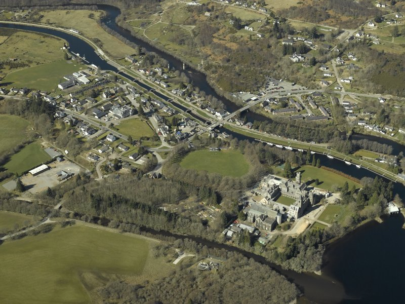 General oblique aerial view of the village centred on the road bridges, swing bridge, locks, abbey and schools, taken from the SE.