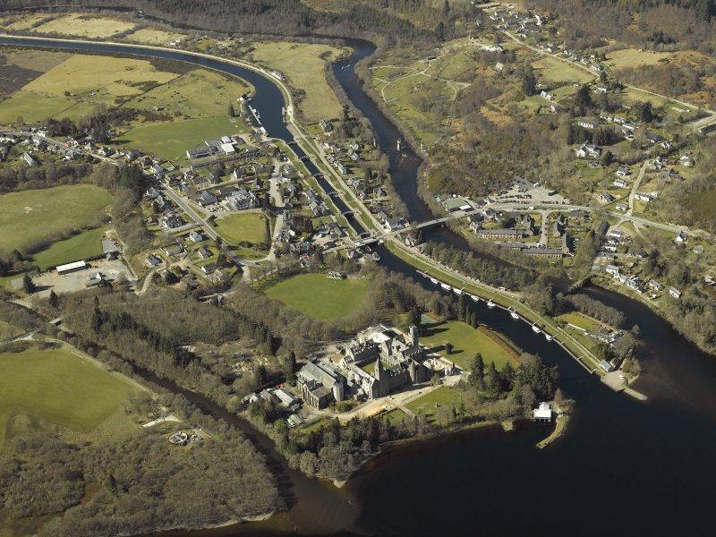 General oblique aerial view of the village centred on the road bridges, swing bridge, locks, abbey and schools, taken from the E.