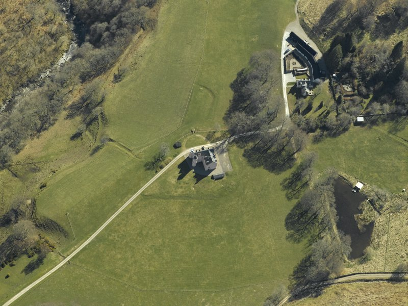 Oblique aerial view centred on the country house, cottage and farmsteading, taken from the NW.