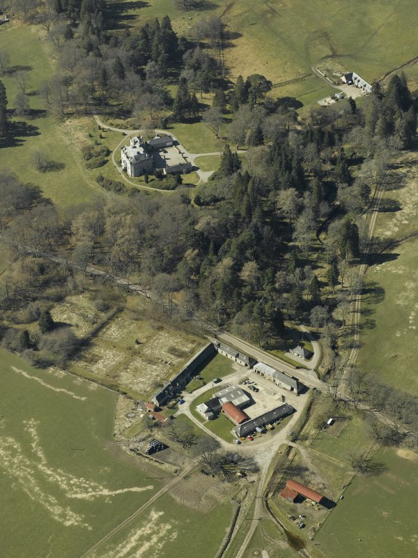 Oblique aerial view centred on the farmsteading, gate-lodge and walled garden with the castle, stable and sawmill adjacent, taken from the E.