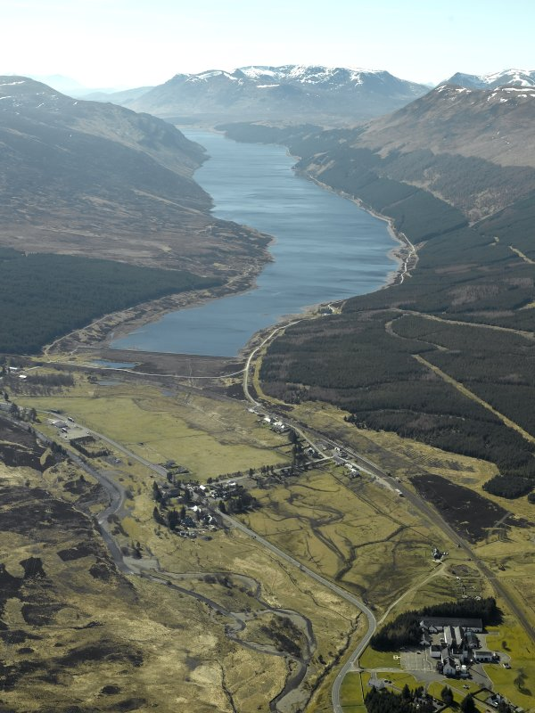 General oblique aerial view of Loch Ericht centred on the dam and the village with Dalwhinnie whisky distillery and bonded warehouse in the foreground, taken from the NE.