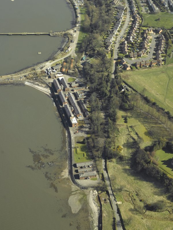 Oblique aerial view centred on the officers' quarters, air raid shelter, stores, boiler house and gym, taken from the W.