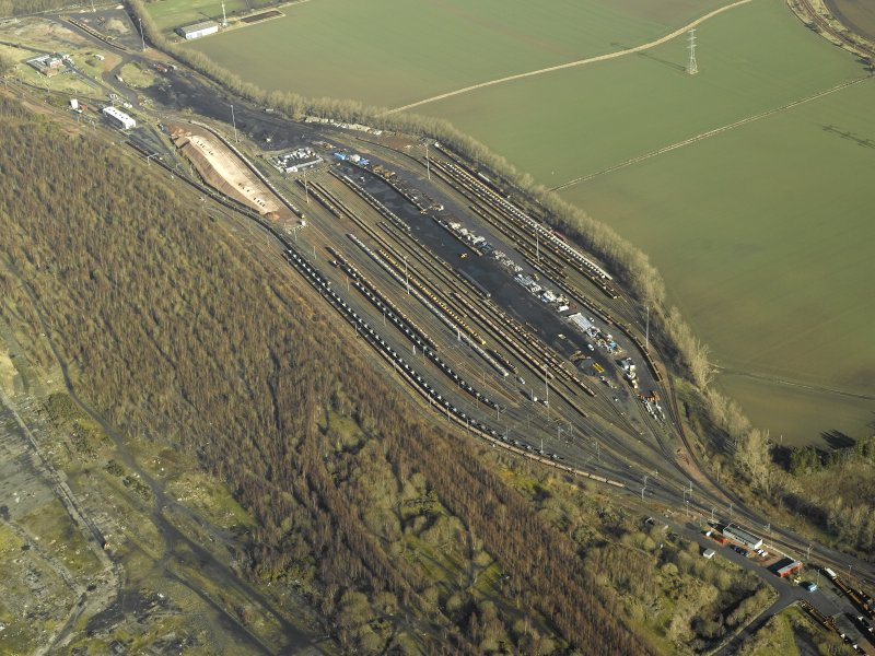 Oblique aerial view centred on railway marshalling yard showing area of former sidings on W side, taken from the SSW.