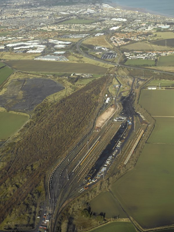 Oblique aerial view centred on railway marshalling yard showing area of former sidings on W side, taken from the SE.