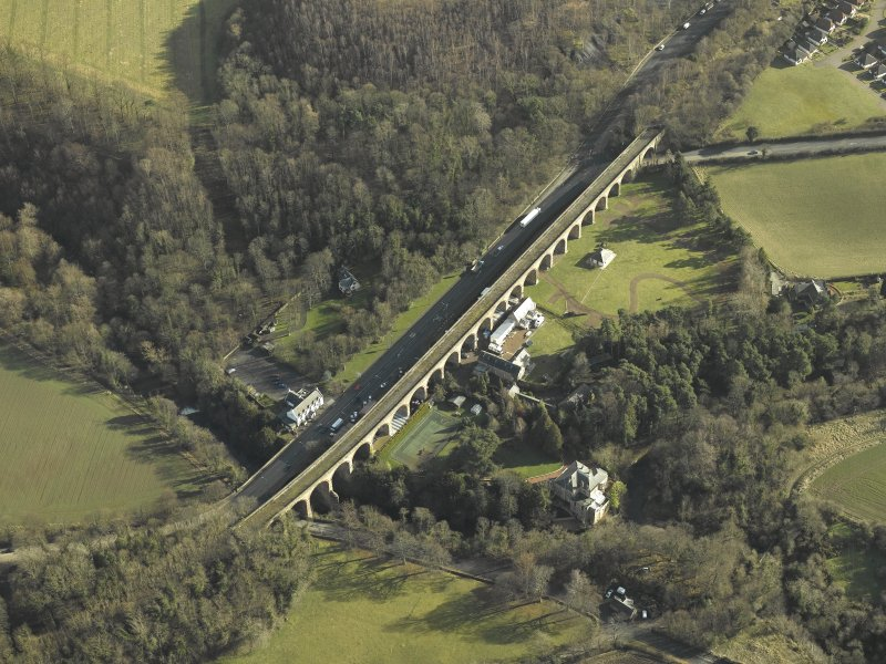 Oblique aerial view centred on Newbattle Railway Viaduct, the Sun Hotel, Lothianbridge, Craigesk House Mill and Damside Cottage, taken from the W.
