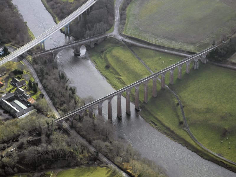 Oblique aerial view centred on the Leaderfoot railway viaduct, Drygrange Bridge and new road bridge, taken from the NW.
