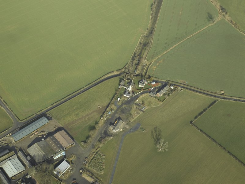Oblique aerial view centred on station buildings, footbridge and road bridge, taken from the S.