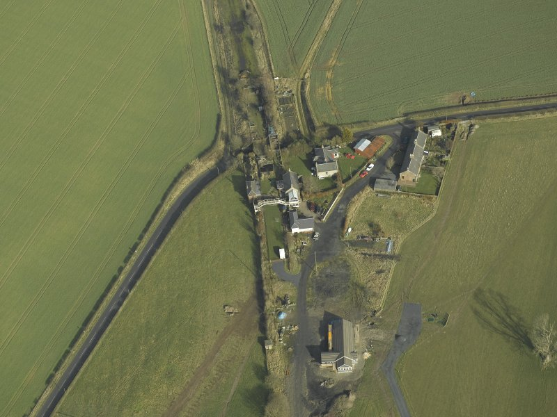 Oblique aerial view centred on station buildings, footbridge and road bridge, taken from the SSW.