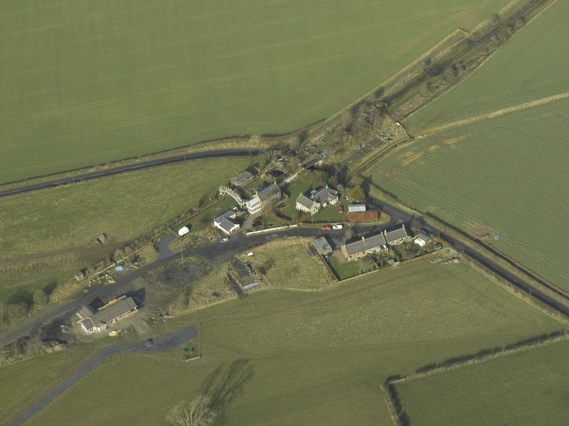 Oblique aerial view centred on station buildings, footbridge and road bridge, taken from the SE.