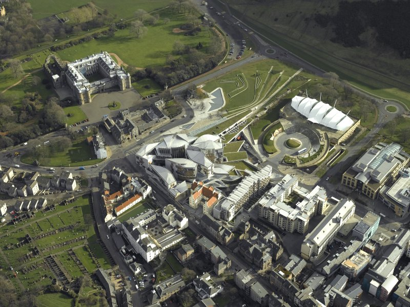 Oblique aerial view centred on Holyrood Palace, Abbey, Parliament building and 'Our Dynamic Earth', taken from the West.