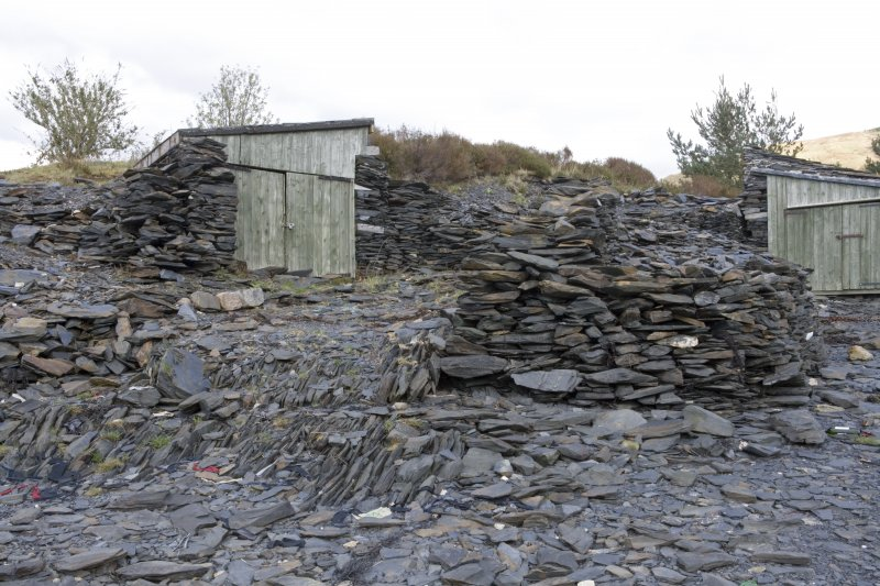 Detail from NE.  Showing modern wooden huts built into slate heaps.