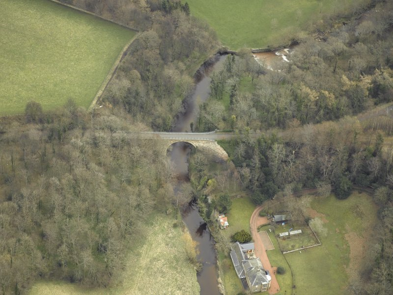 Oblique aerial view centred on the railway viaduct with the house and summer house adjacent, taken from the W.