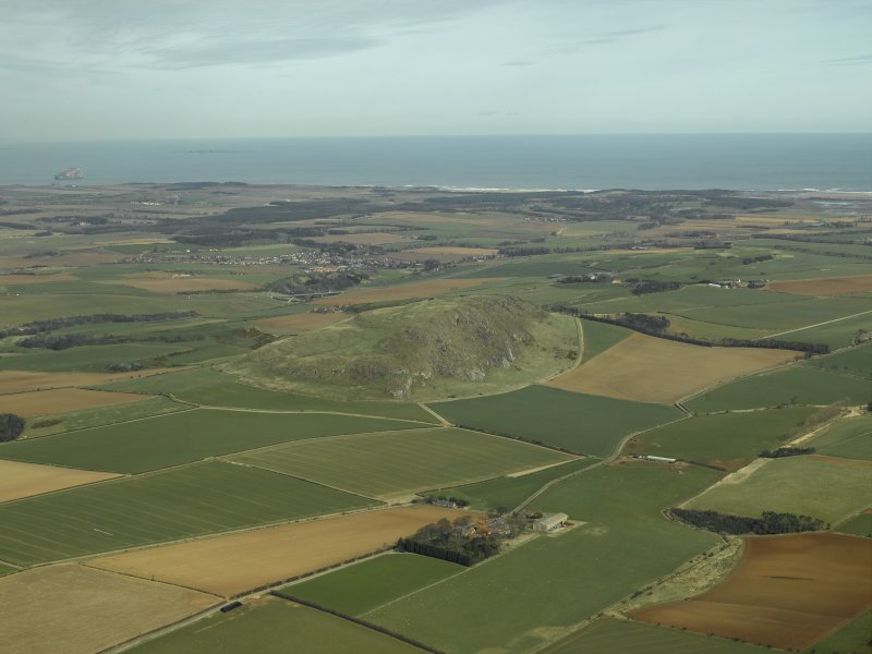 General oblique aerial view centred on the remains of the fort with the village in the distance, taken from the SW.