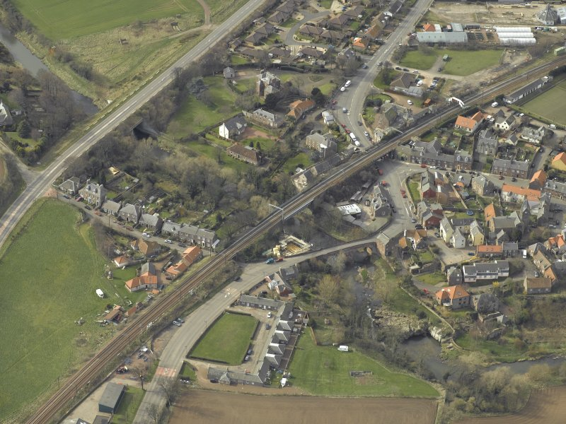Oblique aerial view of the village centred on the road bridges, railway viaduct and church, taken from the ENE.