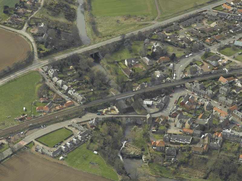 Oblique aerial view of the village centred on the road bridges, railway viaduct and church, taken from the NE.