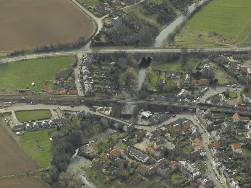 Oblique aerial view of the village centred on the road bridges, railway viaduct and church, taken from the NNE.