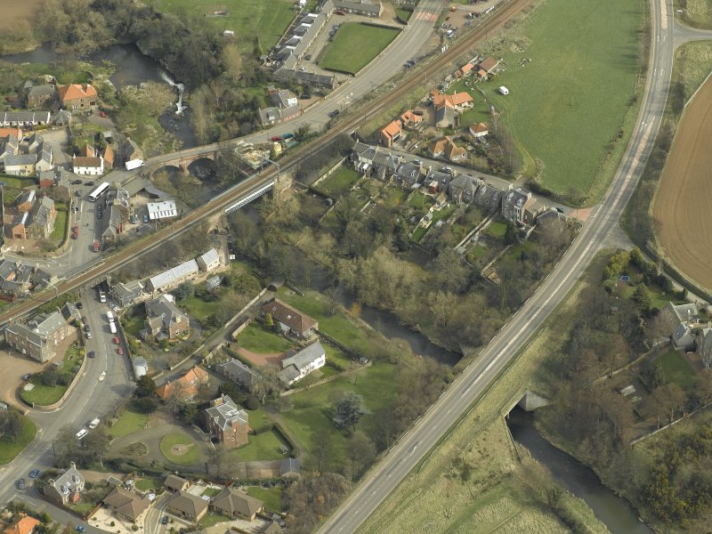 Oblique aerial view of the village centred on the road bridges and railway viaduct, taken from the SW.