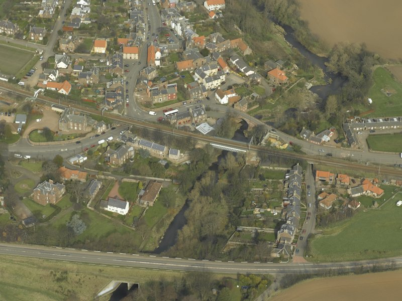 Oblique aerial view of the village centred on the road bridges, railway viaduct and church, taken from the S.