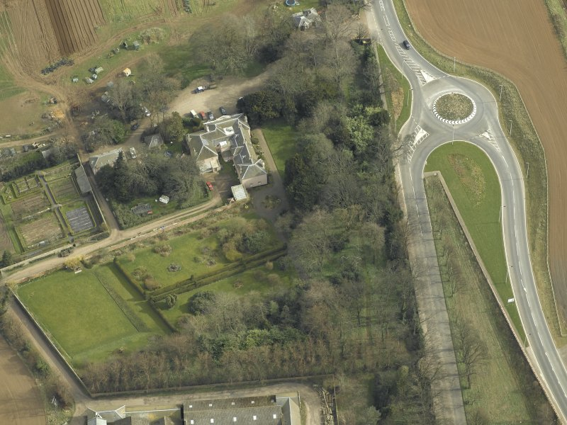 Oblique aerial view centred on the country house with the lodge adjacent, taken from the W.