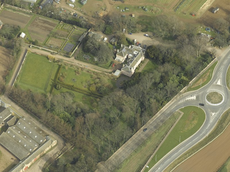 Oblique aerial view centred on the country house with the lodge adjacent, taken from the SW.