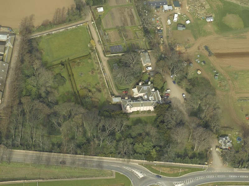 Oblique aerial view centred on the country house with the lodge adjacent, taken from the SE.
