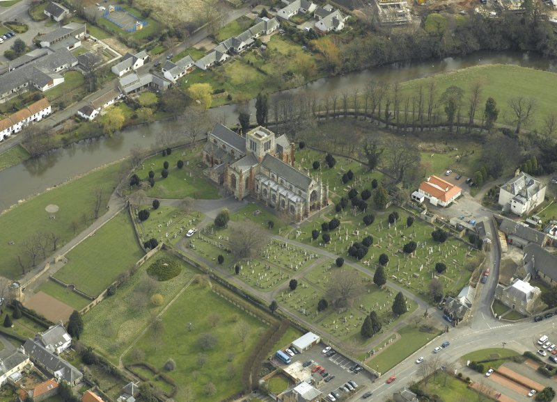 Oblique aerial view centred on the church and the burial-ground, taken from the NW.