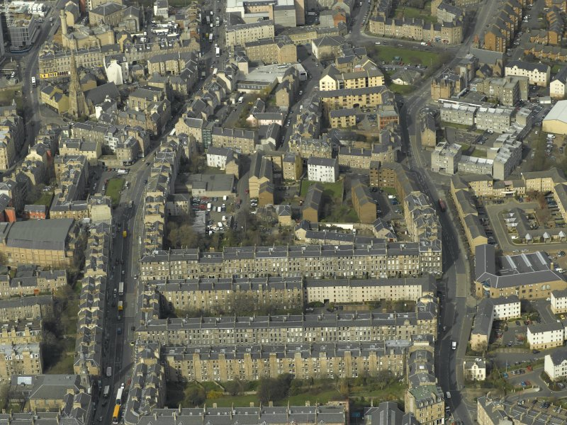 Oblique aerial view of the town centred on the tenement housing with the church adjacent, taken from the SE.