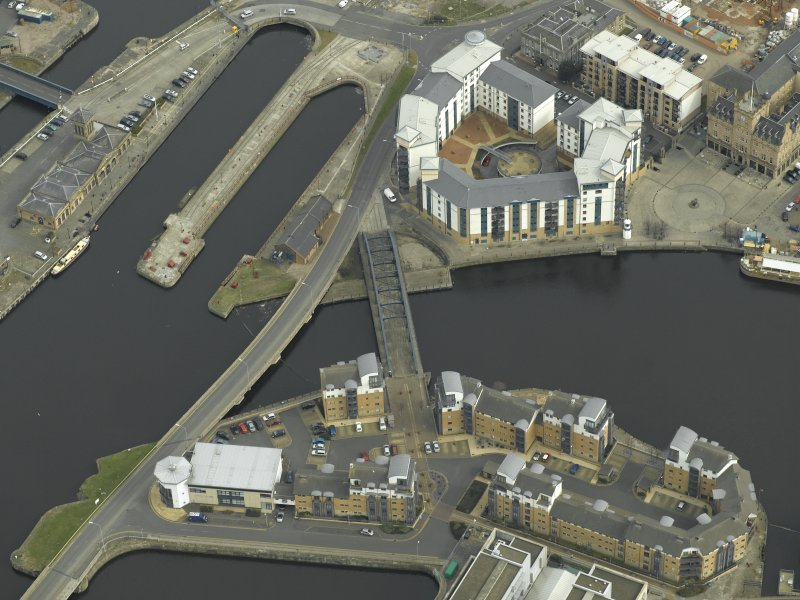 Oblique aerial view centred on the swing bridge, road bridge, harbour, office and dry dock, taken from the WSW.