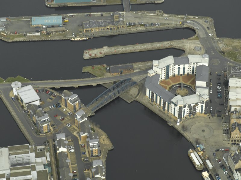 Oblique aerial view centred on the swing bridge, road bridge, harbour, office and dry dock, taken from the SW.
