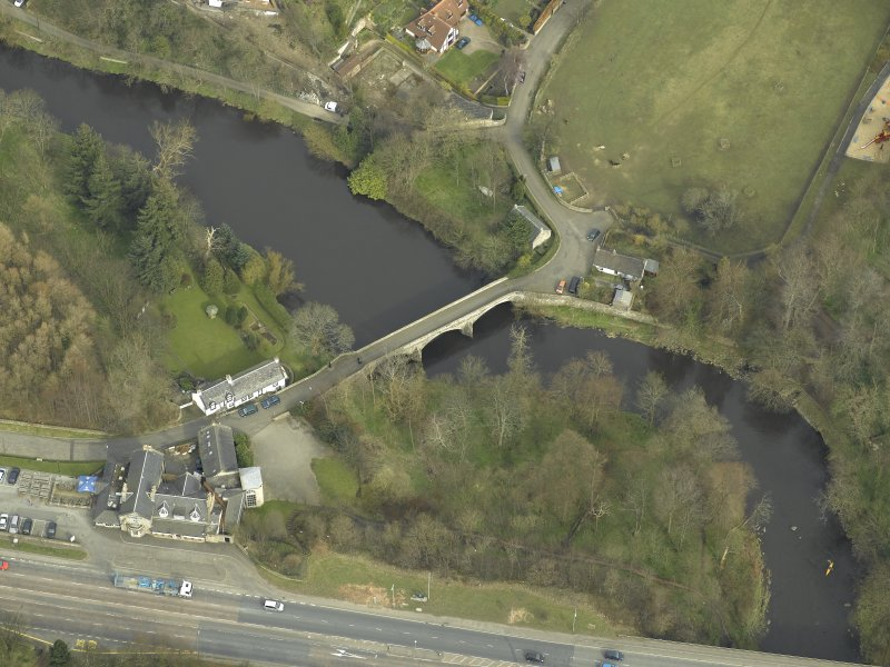 Oblique aerial view centred on the road bridge and cottage, taken from the WSW.