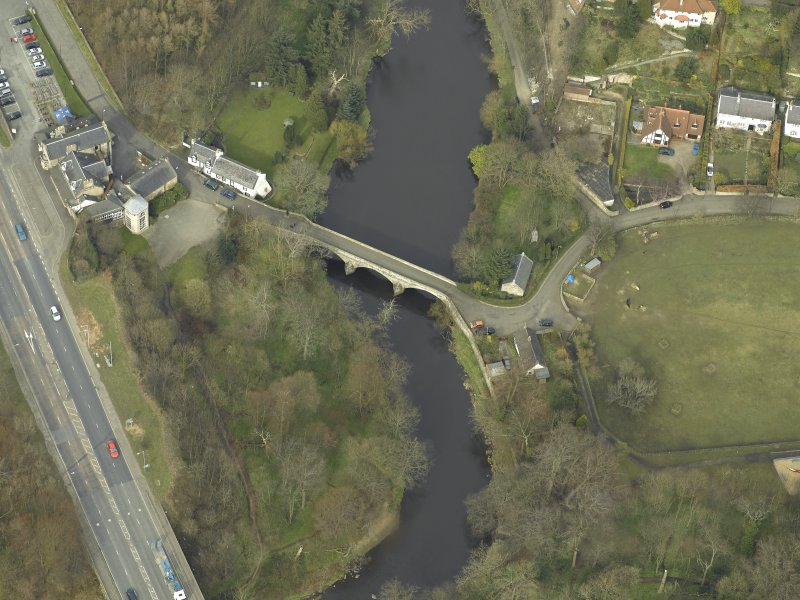 Oblique aerial view centred on the road bridge and cottage, taken from the SSE.