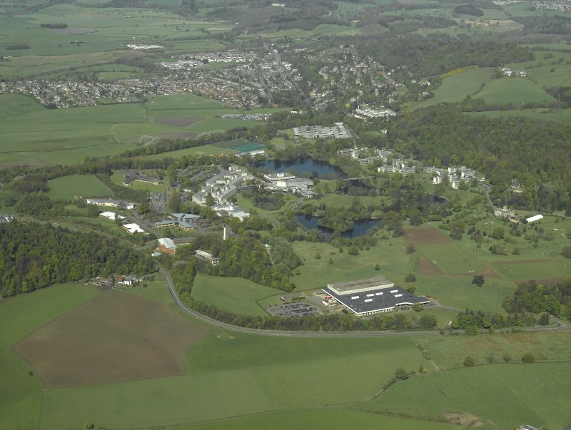 General oblique aerial view centred on the university, library, auditorium, halls of residence, bridge and factory with the country house adjacent, taken from the ESE.