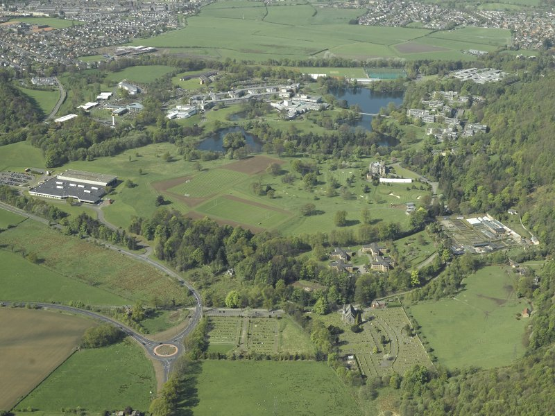 General oblique aerial view centred on the university, library, auditorium, halls of residence, bridge and factory with the church, country house and walled garden in the foreground, taken from the NW.